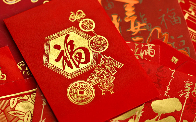 "The Chinese New Year tradition of red packets in exchange for greeting ""Kung Hie Fat Choi"""